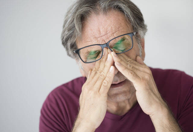 Older man rubbing his eyes