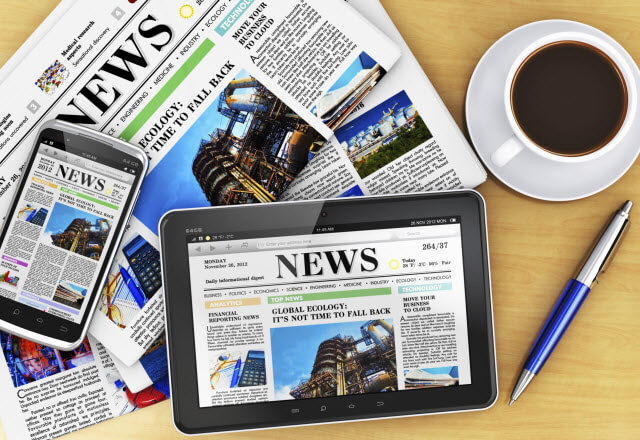A slew of news media laid on top of desk including a tablet news site, mobile phone news site and a physical print newspaper sitting next to a cup of coffee and pen.