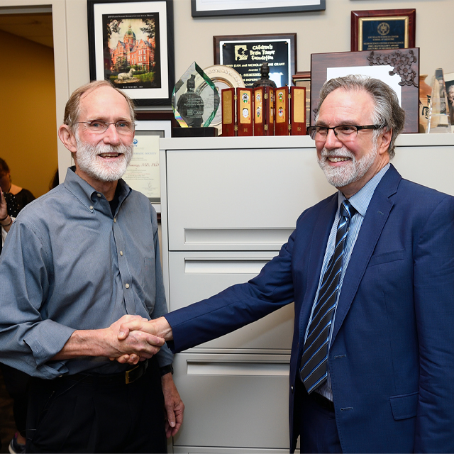 Nobel Laureate Peter Agre, left, congratulates Gregg Semenza on winning the 2019 Nobel Prize in Physiology or Medicine.