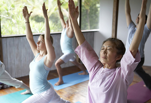 Senior woman demonstrating a yoga position inside a studio.