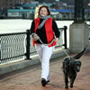 Mary Robertson and her dog walking along a harbor