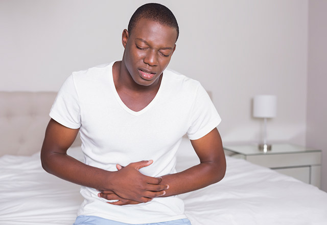 Man clutching his stomach in pain