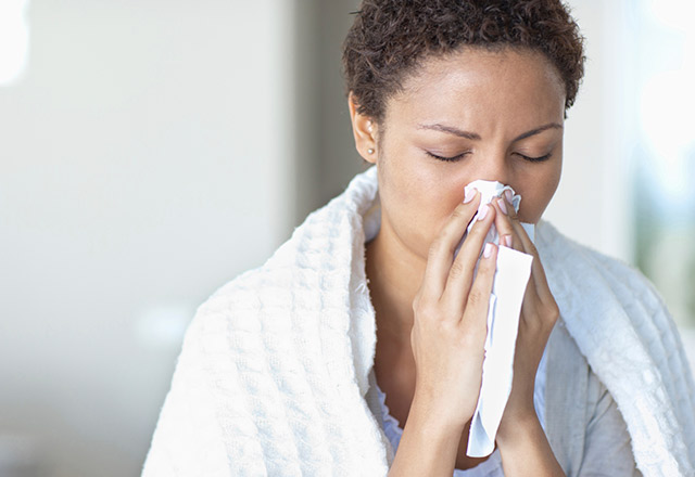 Woman sneezing with the flu