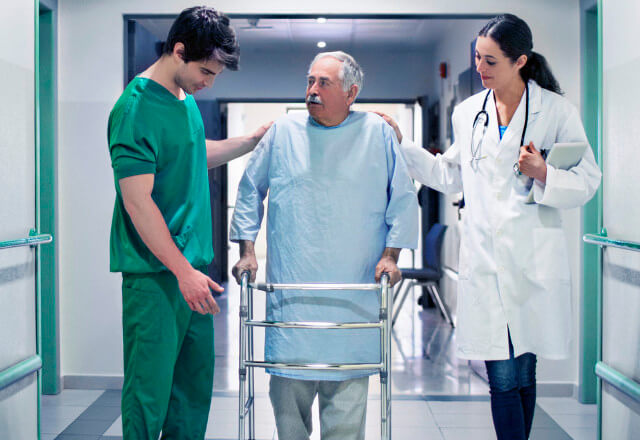 Therapists helping a patient walk down a hospital hallway