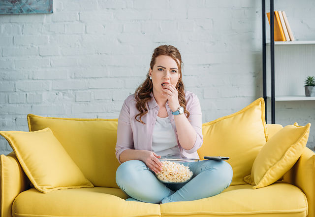 A woman sits on the couch, eating popcorn.