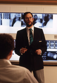 A faculty member lectures from the front of the classroom.