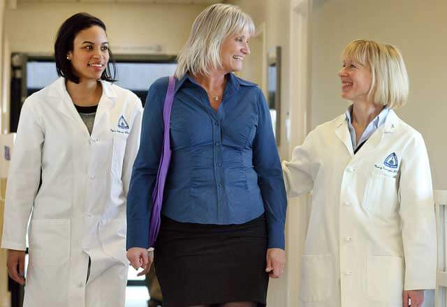 nurses walking with female patient