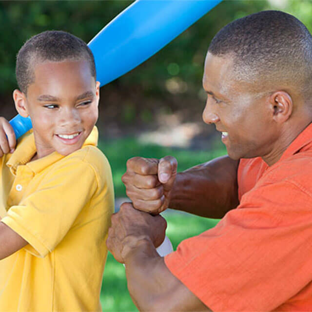 man with son playing baseball