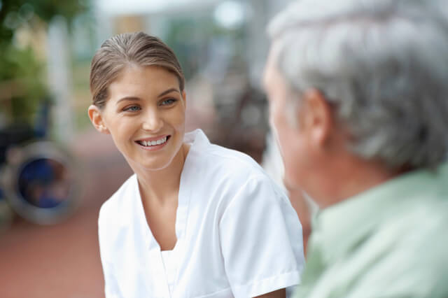 Smiling caregiver talking to patient