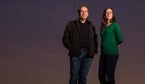 Drs. Andy Feinberg and Lindsay Rizzardi standing in front of a dusk sky