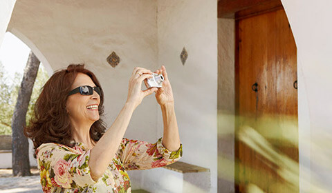 Woman takes a photo while wearing sunglasses