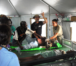 "Thomas Kirsch (holding IV) traveled to Haiti with the Johns Hopkins Go Team to assist earthquake victims, such as the one seen here suffering from shock. The Johns Hopkins team worked in ""austere"" disaster conditions."