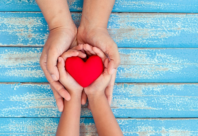 Adult and child hands holding a heart.