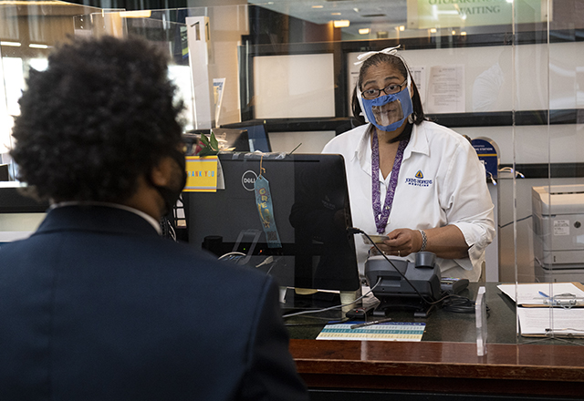 staff wearing plastic face mask while talking to patient