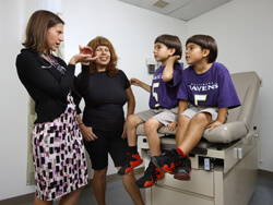 Lisa DeCamp discusses healthy habits with Marlene Aza and her sons, Marlon, left, and Angelo, right.