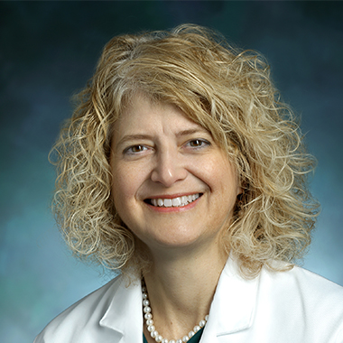 Pediatric neurosurgeon Dody Robinson, in a formal portrait, wearing a white lab coat, green shirt and pearl necklace.