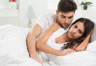 woman, with man, looking unhappy in bed