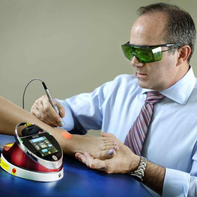 A physical therapist applying laser therapy to a patient's foot
