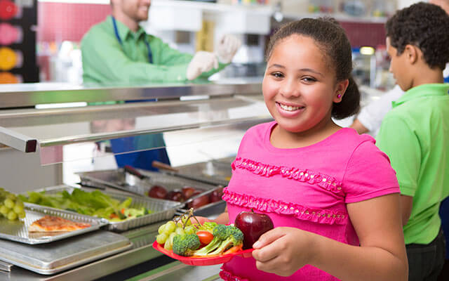 Girl smiling holding a healthy food plate