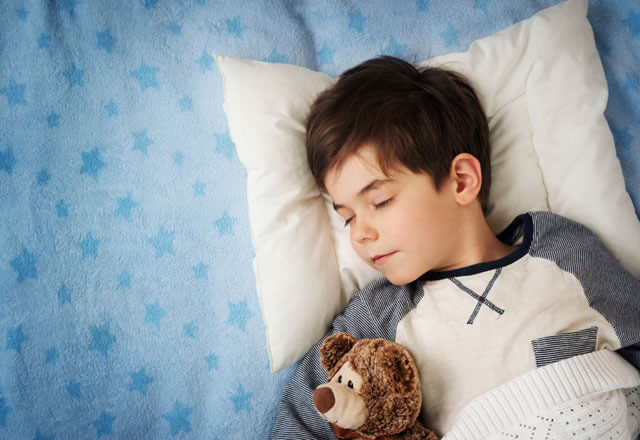 child sleeping peacefully with teddy bear