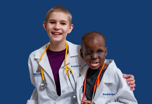 two smiling pediatric patients wearing white physician coats