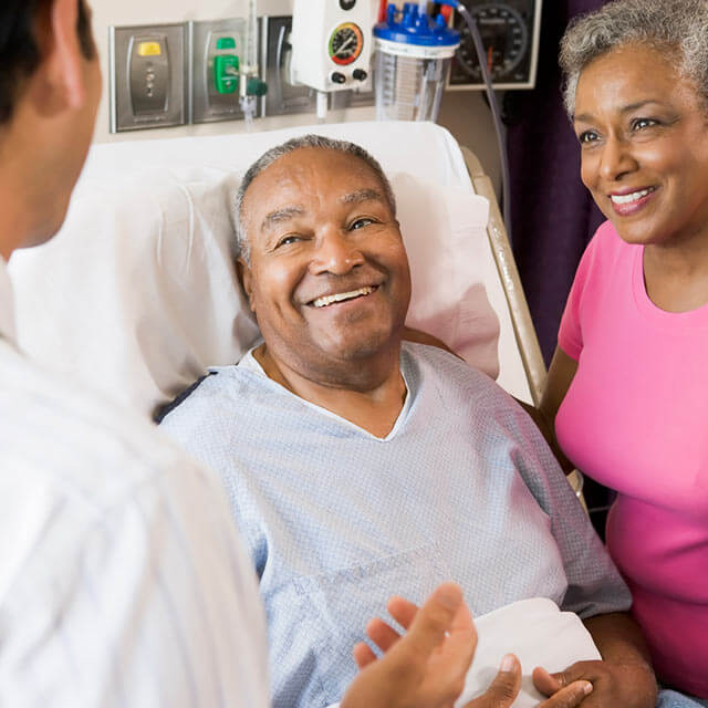 Doctor speaking with a recovering patient and his wife in a hospital room