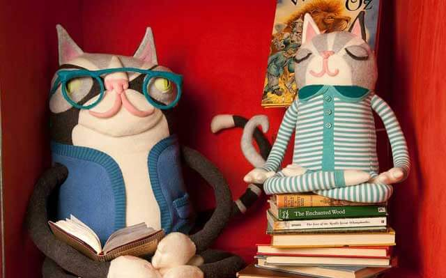 Two cat dolls sitting with books