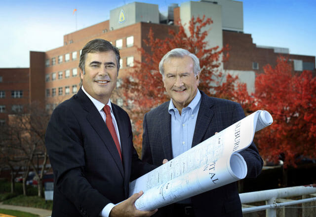 Two men holding architecture drawings in front of Suburban Hospital