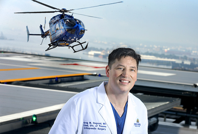 Trauma expert Dr. Osgood on helipad with helicopter landing in background