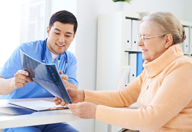 doctor showing film to elderly patient