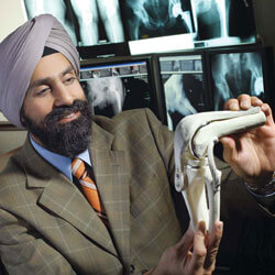 "Harpal ""Paul"" Khanuja, M.D., showing a model of a knee joint"