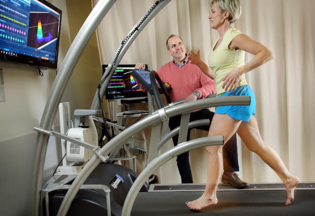 A physical therapist observing a woman running on a treadmill