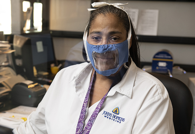 staff wearing plastic face mask