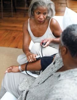 african american woman taking blood pressure of african american man