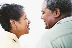 african american man and african american woman looking at each other smiling