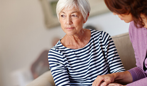 Concerned woman being consoled by caregiver.