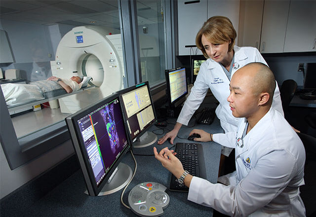 Doctors looking at PET CT reading