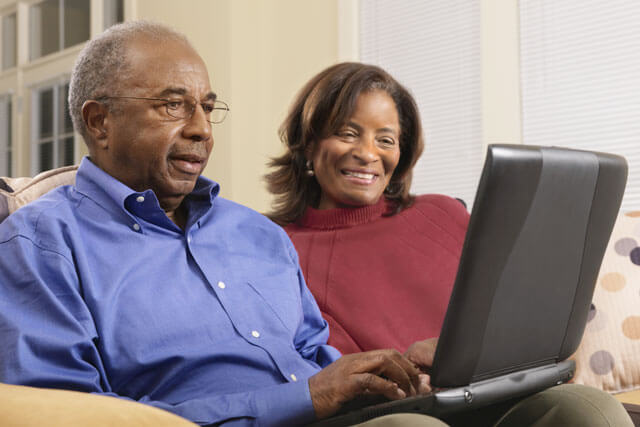 A man and a woman looking up information on a laptop