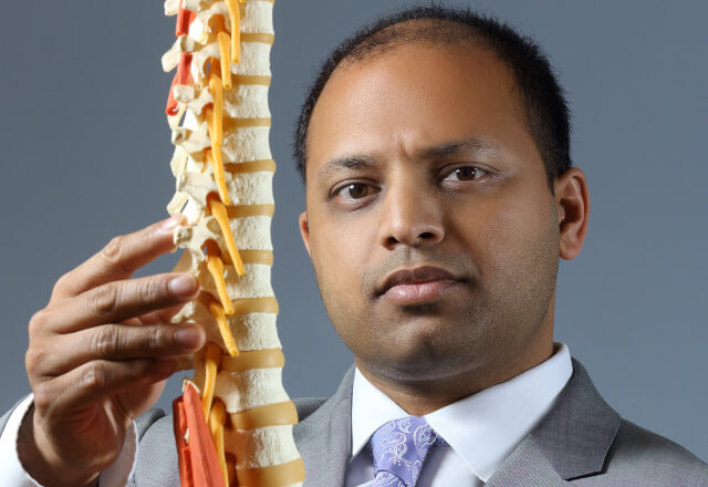 Dr. Chhatre with a model of a spine