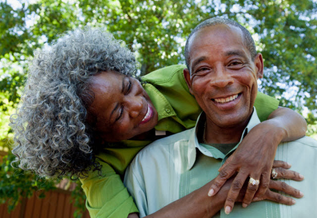 older african-american couple arms around each other