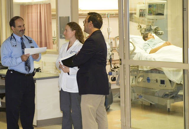 Three doctors consult one another outside of a patient's room