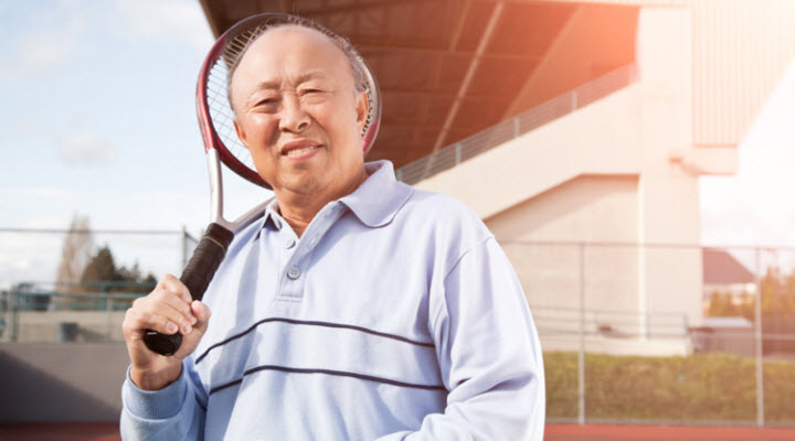 older Asian man holding raquet