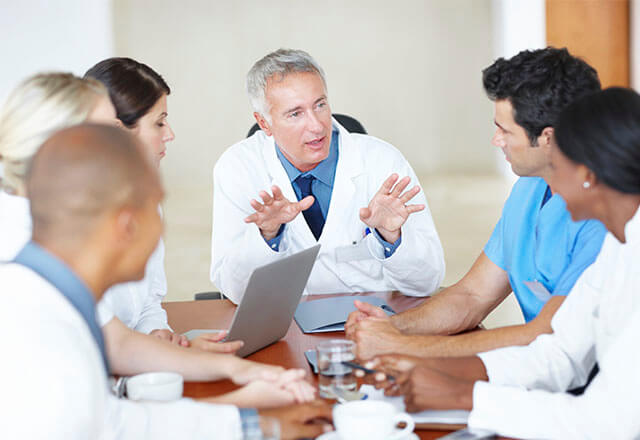 Six clinicians in a conference meeting