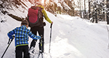 Adult and child snowshoeing up a snowy mountain