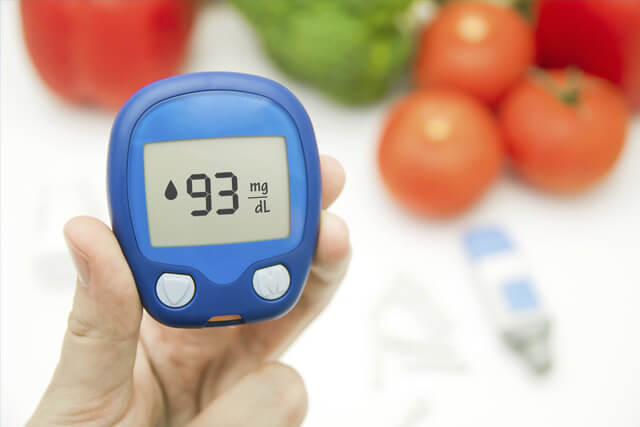 A person holding a blood sugar monitor with healthy food choices in the background