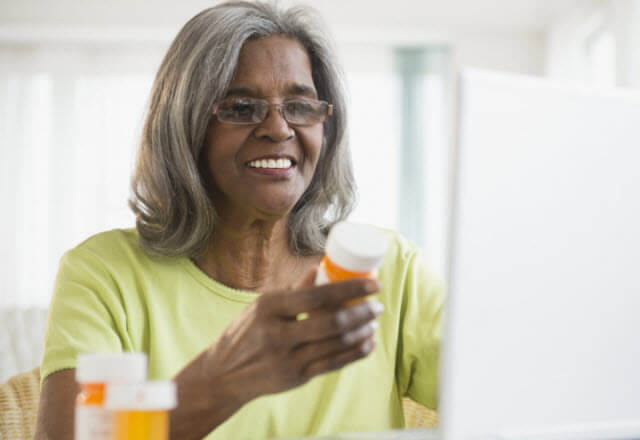 older african-american womna reading prescription label