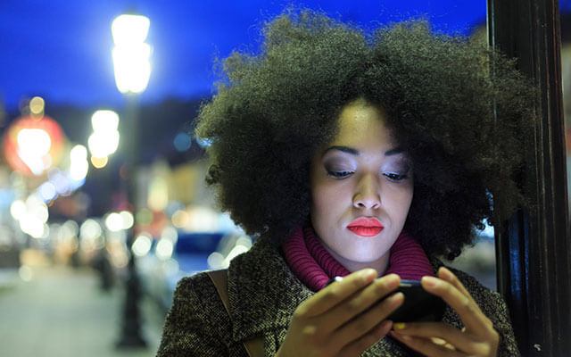 Woman checking her smartphone on a dark winter evening.