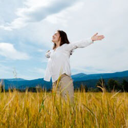 Woman standing in field with arms open