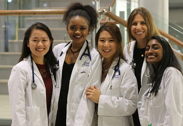 Students pose together wearing their white coats.