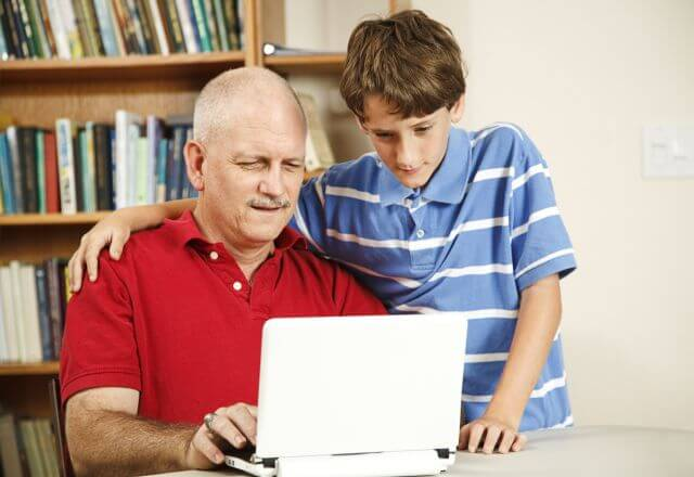 father and son looking at laptop